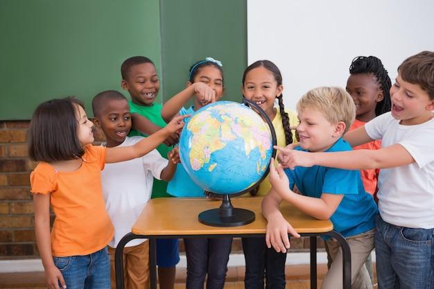 Alunos bonitos apontando para o globo na sala de aula