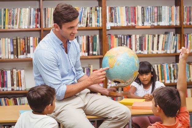 Alunos bonitos e professor que olham o globo na biblioteca