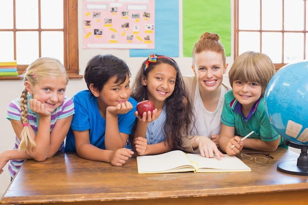 Alunos bonitos e professor sorrindo para a câmera na sala de aula