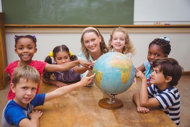 Alunos bonitos e professores em sala de aula com globo