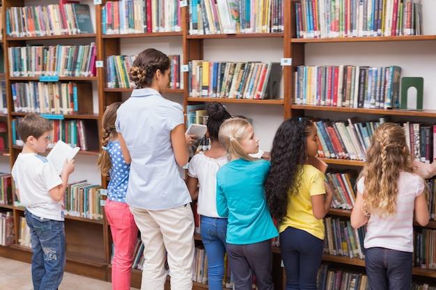 Alunos bonitos e professores que procuram livros na biblioteca