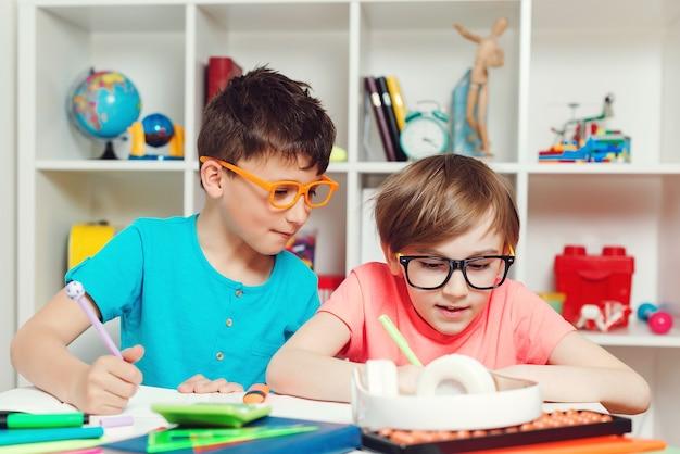 Alunos bonitos escrevendo na mesa em sala de aula. educação, escola primária. aluno fazendo teste na escola primária.