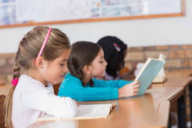 Alunos bonitos lendo livros em suas mesas