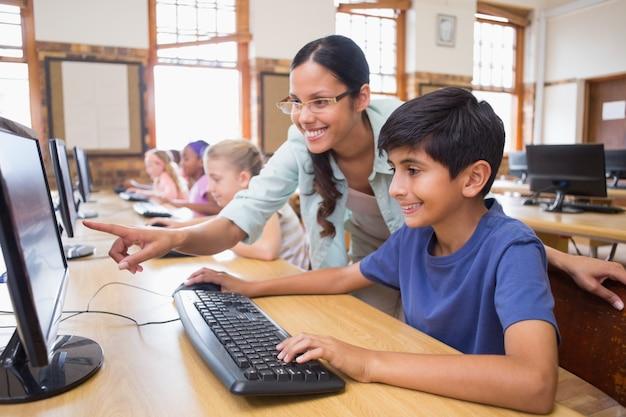 Alunos bonitos na aula de informática com professor na escola primária