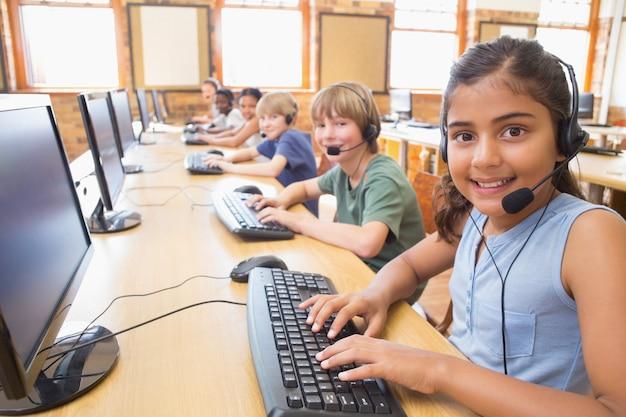 Alunos bonitos na aula de informática na escola primária
