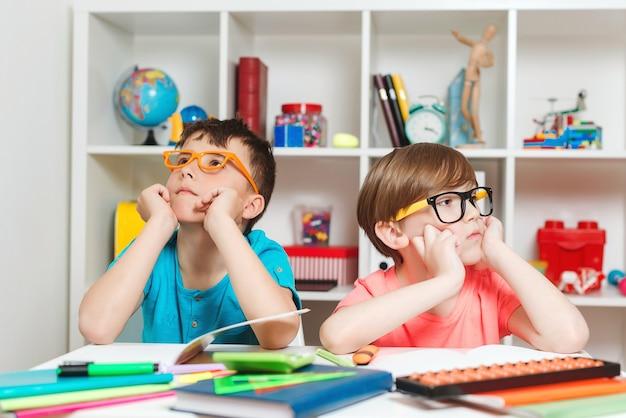 Alunos bonitos no local de trabalho da classe. meninos pensativos sentados à mesa.