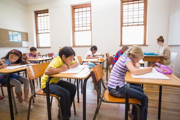 Alunos bonitos que escrevem na mesa na sala de aula