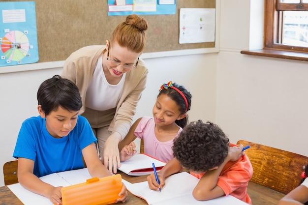 Alunos bonitos recebendo ajuda do professor na sala de aula