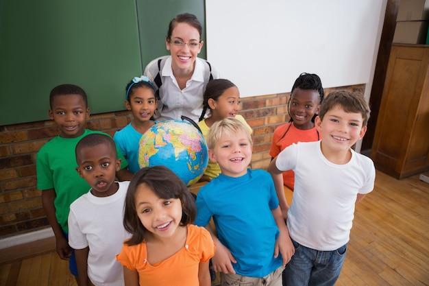 Alunos bonitos sorrindo ao redor de um globo na sala de aula com professor