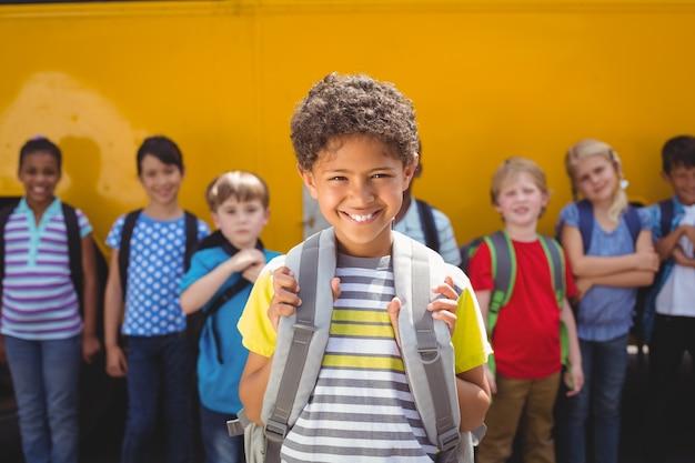 Alunos bonitos sorrindo para a câmera pelo ônibus escolar