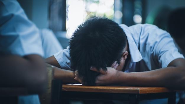 Alunos cansados de uniforme dormindo em um teste de exame em sala de aula com estresse