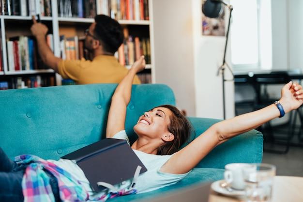 Alunos cansados jovens atraentes homem e mulher aprendendo e descansando na biblioteca da universidade e aprendendo.