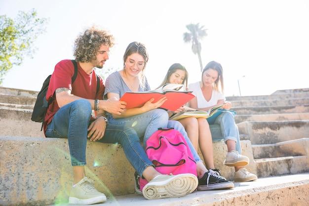 Alunos com mochila lendo em etapas