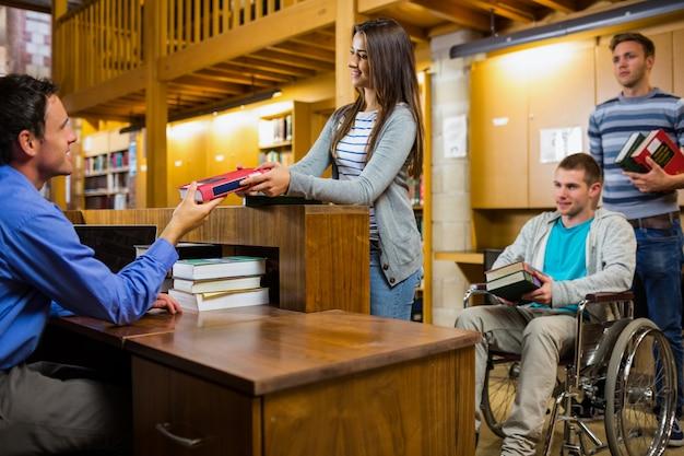 Alunos com o homem deficiente no balcão da biblioteca