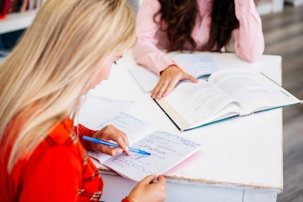 Alunos completando o dever de casa na mesa