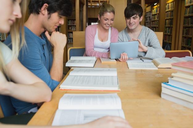 Alunos da biblioteca estudando com dois usando o tablet pc