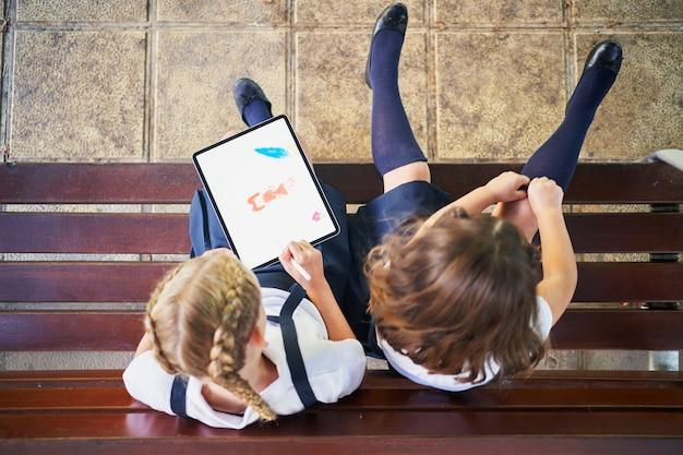 Alunos da escola espanhola desenhando em um tablet no parque