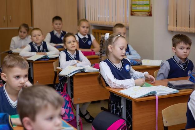 Alunos da escola primária em suas carteiras na sala de aula