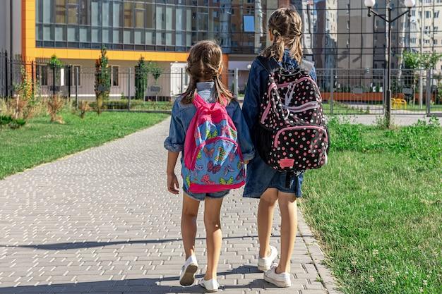 Alunos da escola primária meninas com mochilas perto da escola ao ar livre