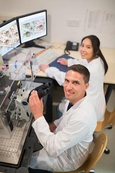 Alunos de bioquímica usando microscópio grande e computador