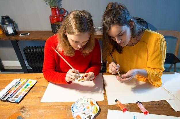 Alunos de escola de arte focada aprendendo pintura
