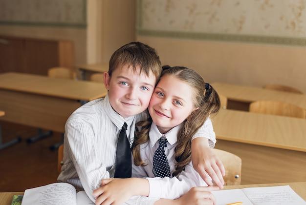 Alunos de menino e menina desfrutam sentado em uma mesa. o menino puxa as tranças da menina.