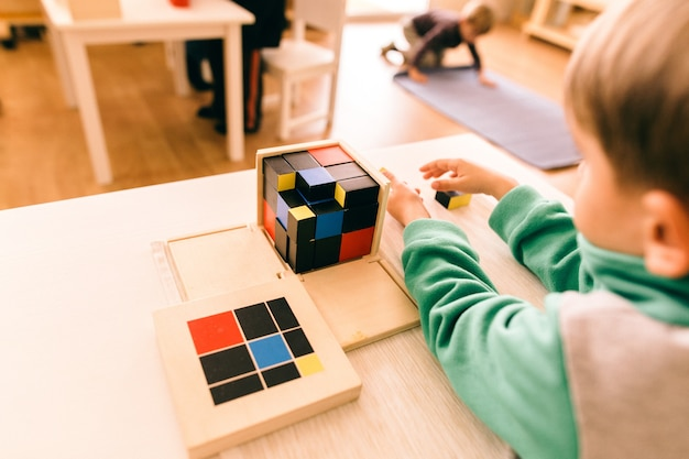 Alunos de meninos e meninas em uma escola montessoriana manipulando seu material para aprender