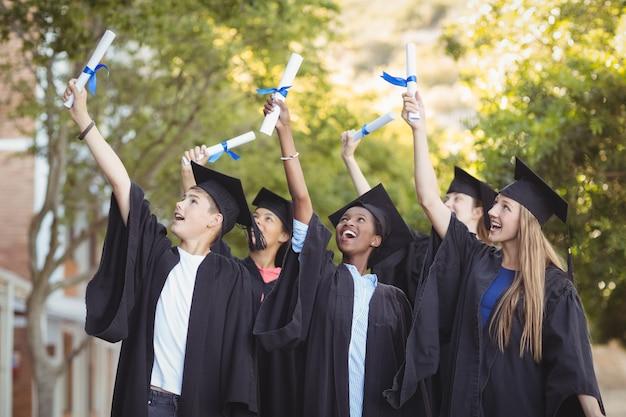 Alunos de pós-graduação sorridentes em pé com a rolagem de diplomas no campus
