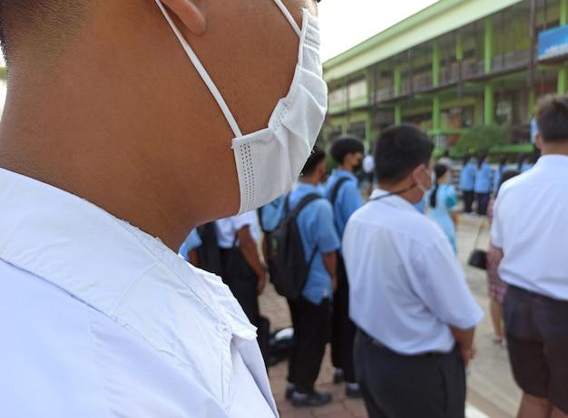 Alunos de uniformes asiáticos em pé no semestre começam usando máscaras