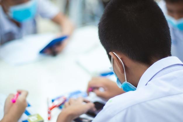 Alunos de uniformes asiáticos usam uma máscara, com a intenção de estudar na sala de aula.