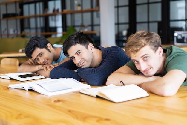 Alunos descansando na mesa com livros didáticos e olhando para a câmera