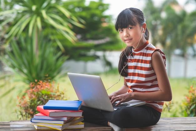 Alunos do ensino fundamental na ásia sentam-se e estudam à distância de casa. conceito de educação on-line