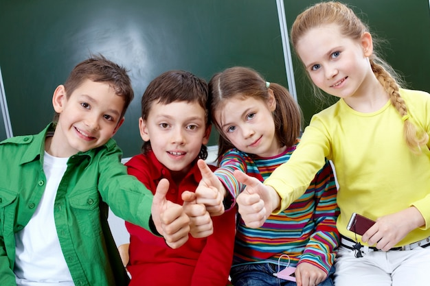 Alunos do ensino primário com polegares acima