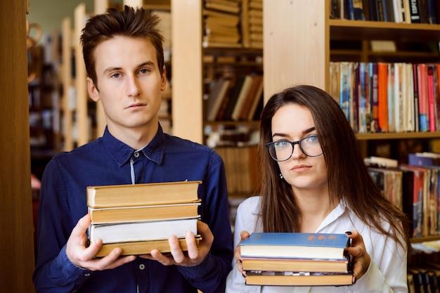 Alunos do sexo masculino e feminino doentes e cansados com muitos livros nas mãos em pé na biblioteca