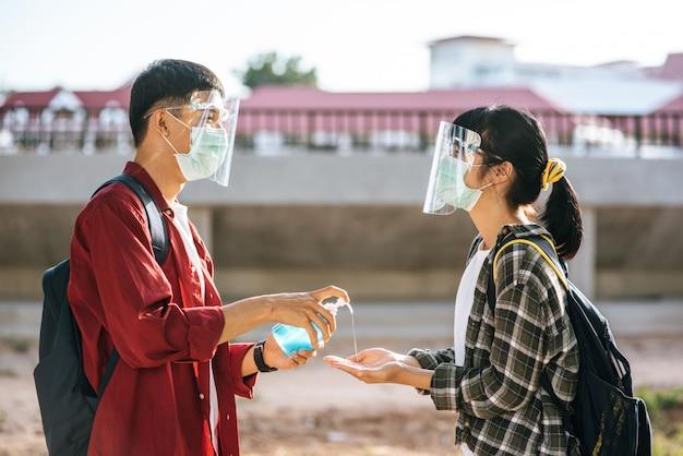 Alunos do sexo masculino e feminino usam máscaras e apertam o gel para lavar as mãos.