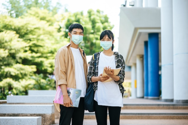 Alunos do sexo masculino e feminino usam uma máscara de saúde e conversam entre si na escada.