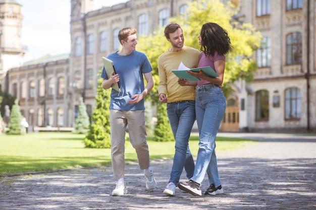 Alunos. dois garotos e uma garota caminhando e discutindo exames futuros