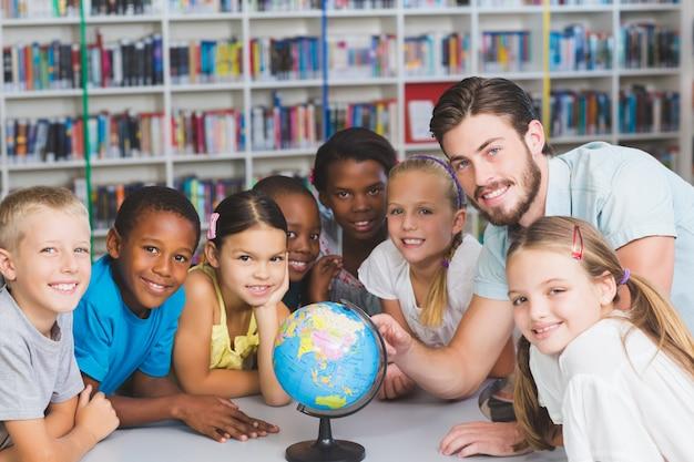 Alunos e professor olhando o globo na biblioteca