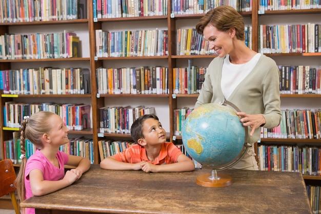 Alunos e professor, olhando para o globo na biblioteca
