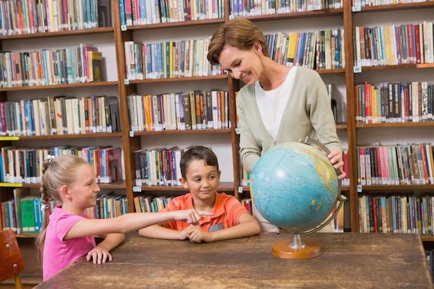 Alunos e professores que olham o globo na biblioteca