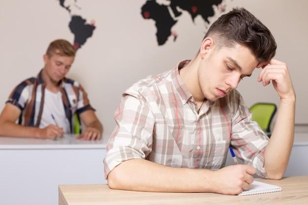 Alunos em sala de aula com o mapa do mundo na parede