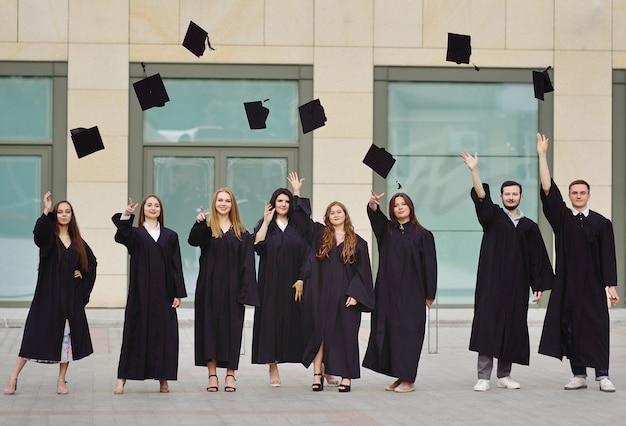 Alunos em túnicas levantam bonés acadêmicos e ficam felizes em receber educação superior.