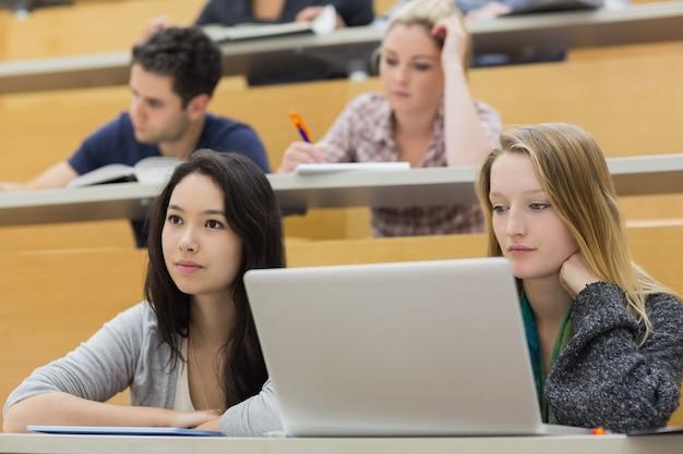 Alunos em uma sala de aula usando um laptop