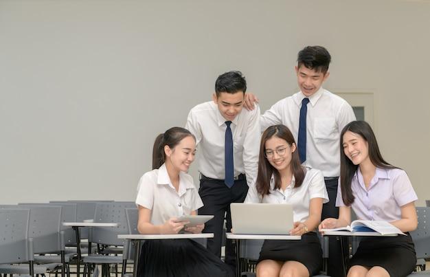 Alunos em uniforme trabalhando com laptop