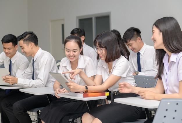 Alunos em uniforme trabalhando com tablet em sala de aula