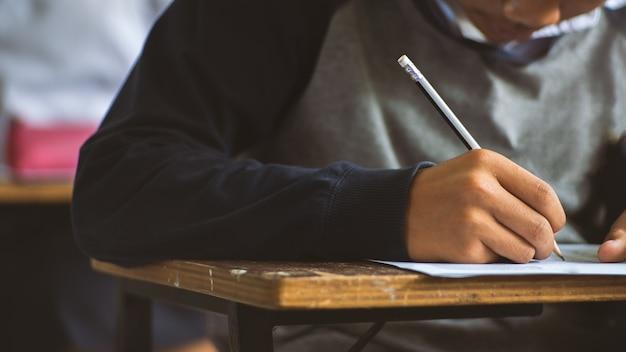 Alunos escrevendo a caneta na mão fazendo exames de folhas de respostas exercícios em sala de aula com stress.16: 9 estilo