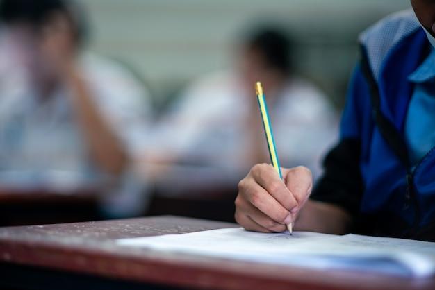Alunos escrevendo e lendo exercícios de folhas de respostas para exames na sala de aula da escola com estresse