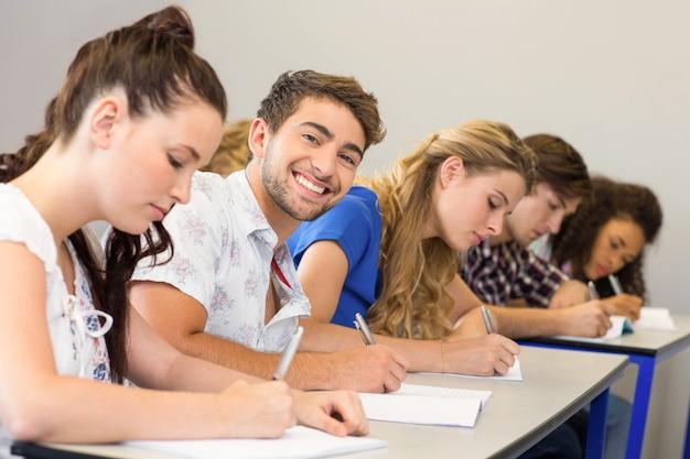 Alunos escrevendo notas em sala de aula