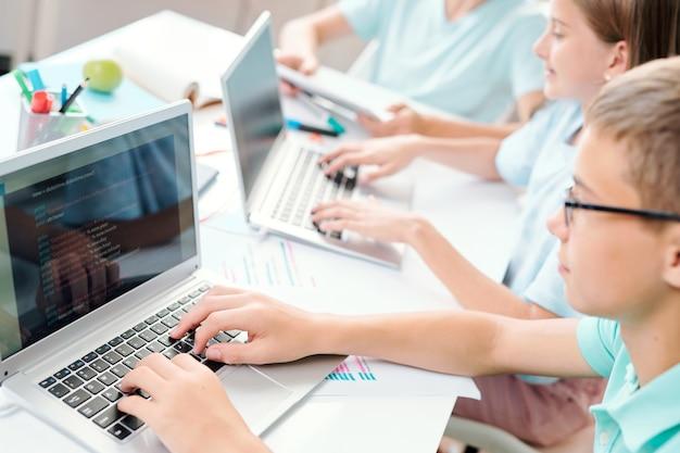 Alunos espertos do ensino fundamental tocando as teclas do teclado do laptop enquanto trabalham individualmente na mesa da aula