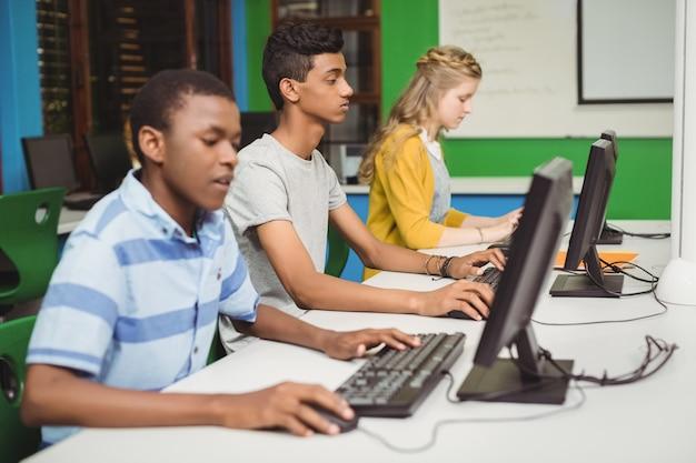 Alunos estudando em sala de aula de informática